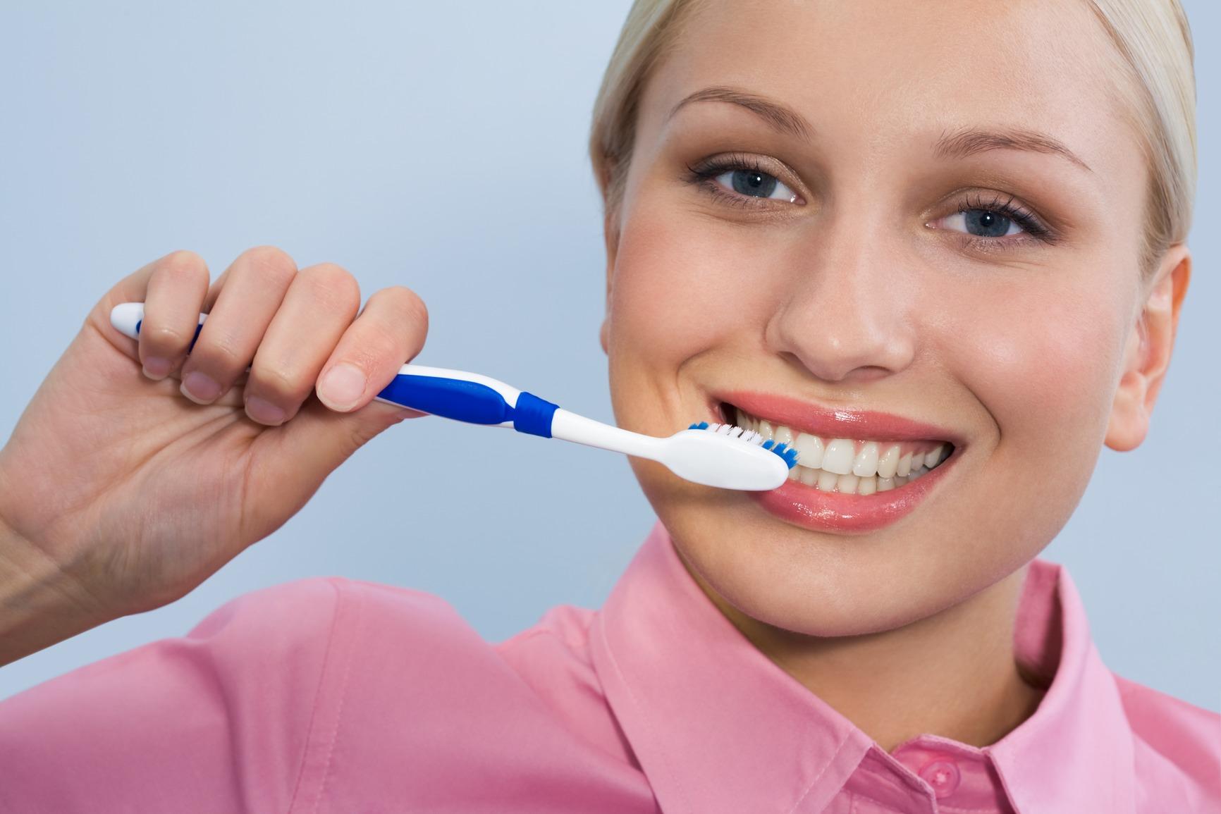 Femeie blonda care se spala pe dinti pentru a preveni aftele bucale