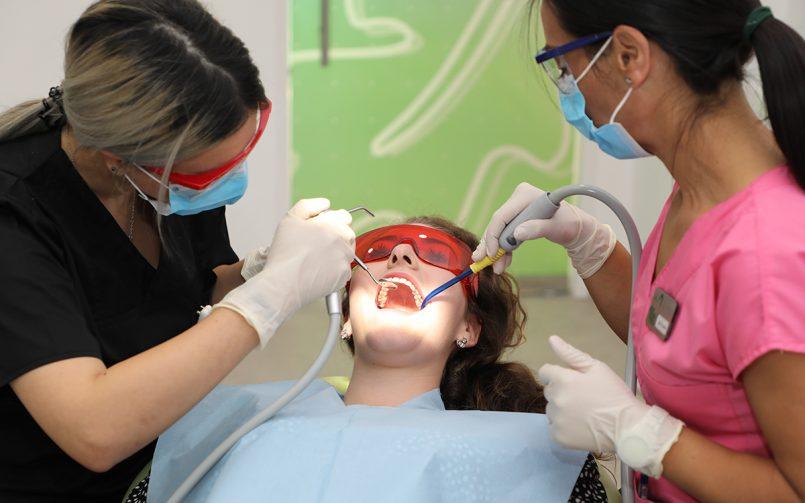 Tânără la stomatolog, în timp ce medicul îi face detartraj