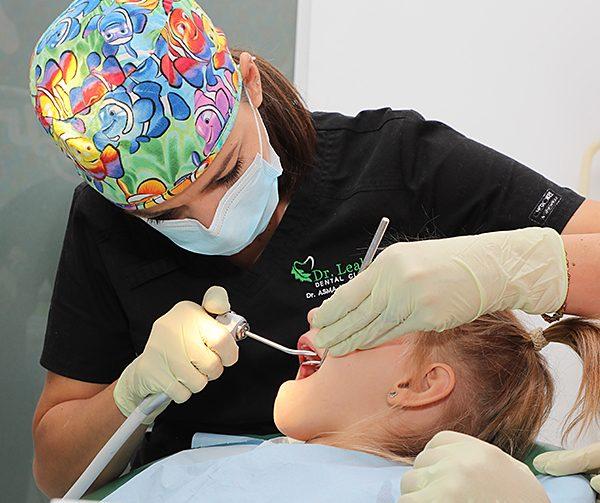 Medic stomatolog care trateaza o fetita cu carie de biberon