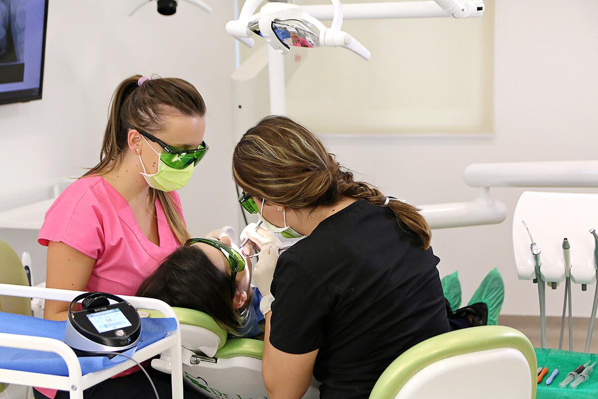 Medic si asistenta alaturi de pacient, in timpul unui tratament de stomatologie laser