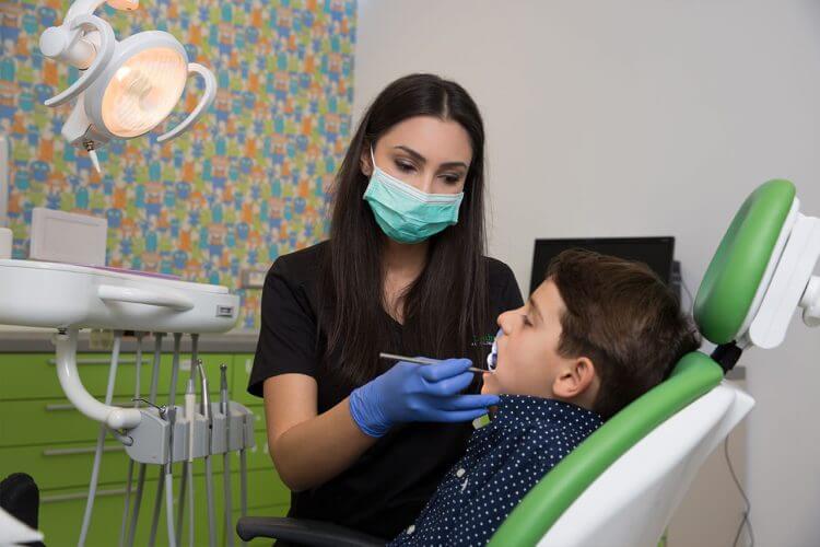 Medic stomatolog pediatru tratând un copil în cabinet
