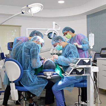 Echipa de medici stomatologi, refacand dantura unui pacient cu ajutorul unor implanturi dentare Sky Fast and Fixed de la Bredent