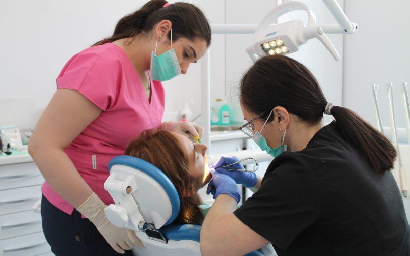 Medic si asistenta in timpul aplicării unui aparat dentar, în cabinetul stomatologic