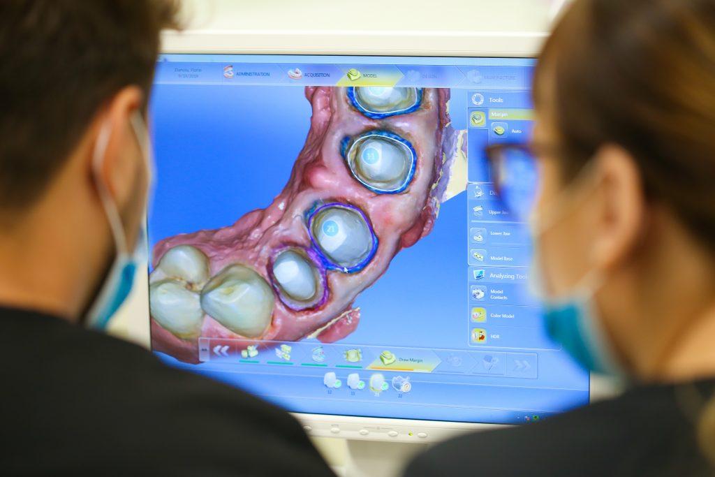Medici care privesc un monitor ce indica tehnologia pentru lucrările dentare