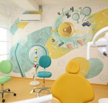 Cabinet dentar de la Academia spatiala Dr Leahu Victoriei, cu scaune colorate în galben și verde și un perete decorat cu desene de imită spațiul cosmic