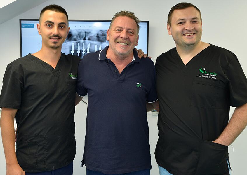 Dr. Ionut Leahu, in cabinet, zambind alaturi de un coleg medic stomatolog si un pacient fericit