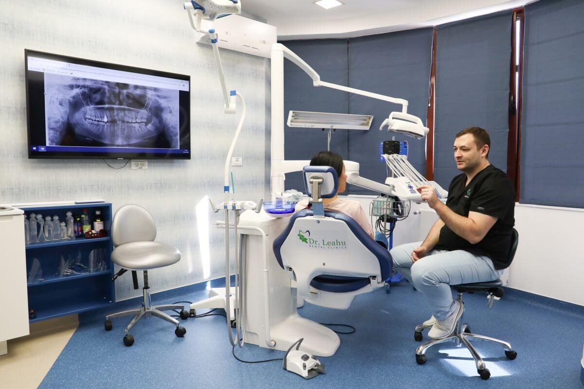 Dr. Ionuț Leahu, alaturi de o pacienta in cabinet, in Clinica Stomatologica Dr. Leahu Caramfil din Bucuresti