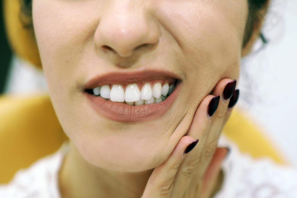 durere de dinte indicata de o femeie cu mana stanga in zona obrazului