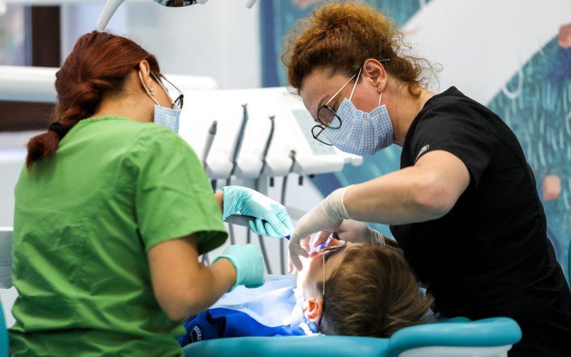 periaj dentar profesional copii realizat de catre medic pedodont in dreapta si asistenta in stanga