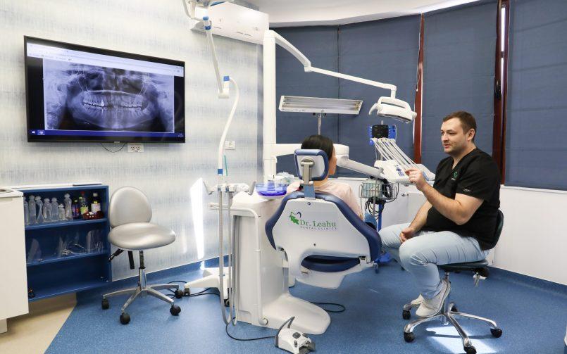 medic stomatolog in dreapta si pacient pe scaun in timpul consultației pentru limba albă