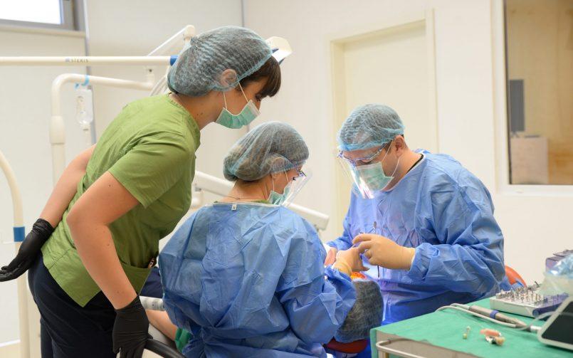 medici stomatologi si asistenta in timpul inserarii implanturilor dentare