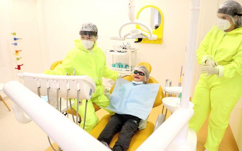 medic pedodont în stanga și asistentă în dreapta în timpul unui tratament pentru urgente stomatologice la copii