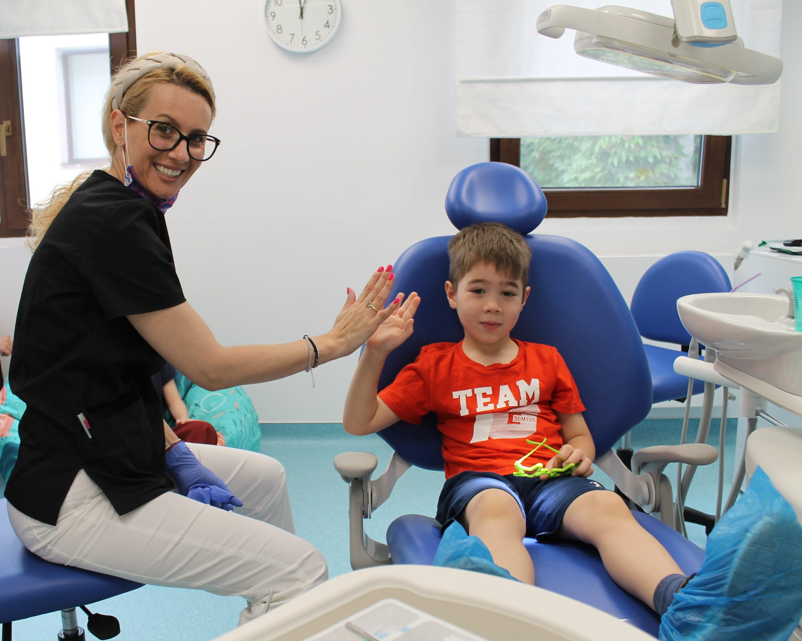 Dr. Mihaela Parlog in stanga pe scaun bate palma cu pacientul din dreapta, pe scaunul stomatologic