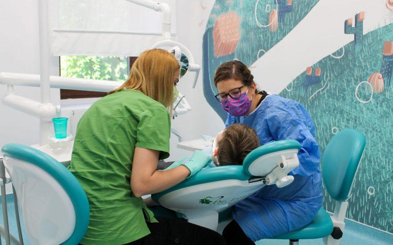 Dr. Ariela Pana in dreapta scaunului stomatologic si asistenta in stanga scaunului stomatologic in timpul unei interventii la copii