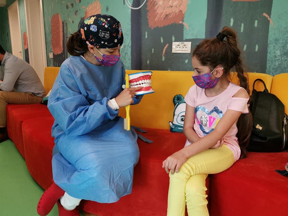 Dr. Asma Battah in stanga pe canapea explica cum se face periajul dentar pacientei din dreapta