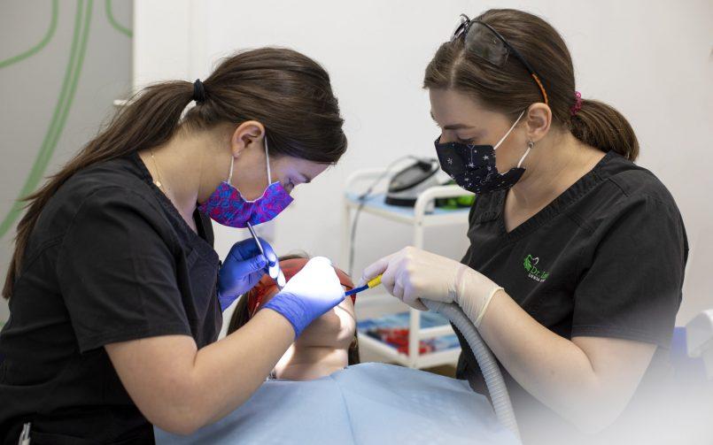 Medic in stanga si in dreapta care folosesc tratamentul cu laser pentru stomatologie