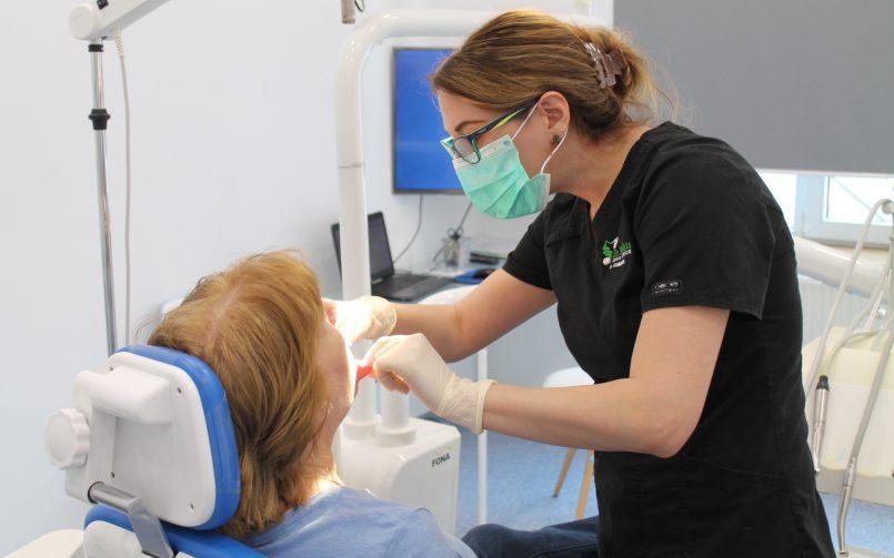 Diverse tipuri de proteze dentare încercate de catre Dr. Corina Ene in dreapta pacientei de pe scaunul stomatologic