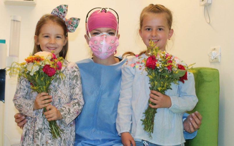 medic pedodont impreuna cu doi pacienti in stanga si in dreapta dupa tratarea afectiunilor dentare la copii