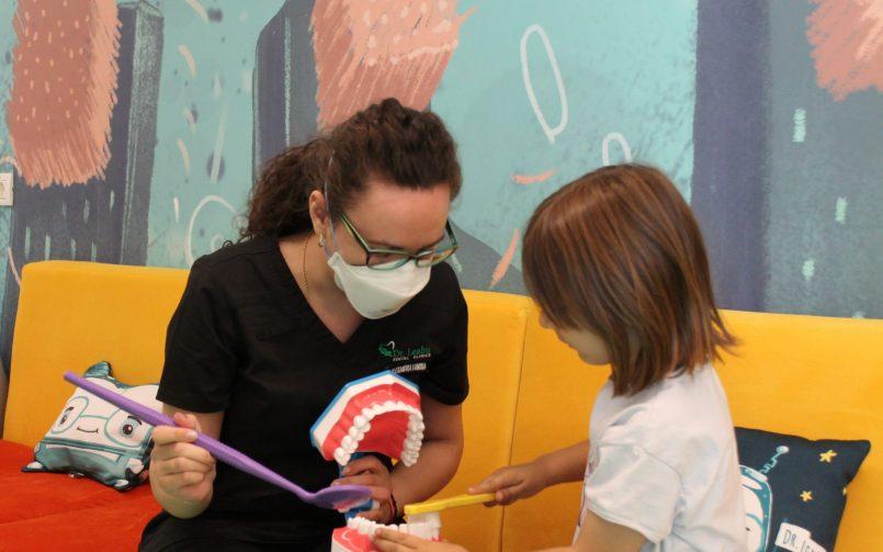 Periajul dentar explicat de c[tre medic pedodont in stanga unui copil