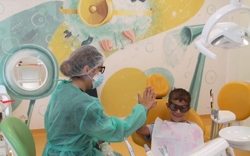 pacient pe scaunul stomatologic si medic in stanga dupa un tratament pentru dinti de lapte cariati