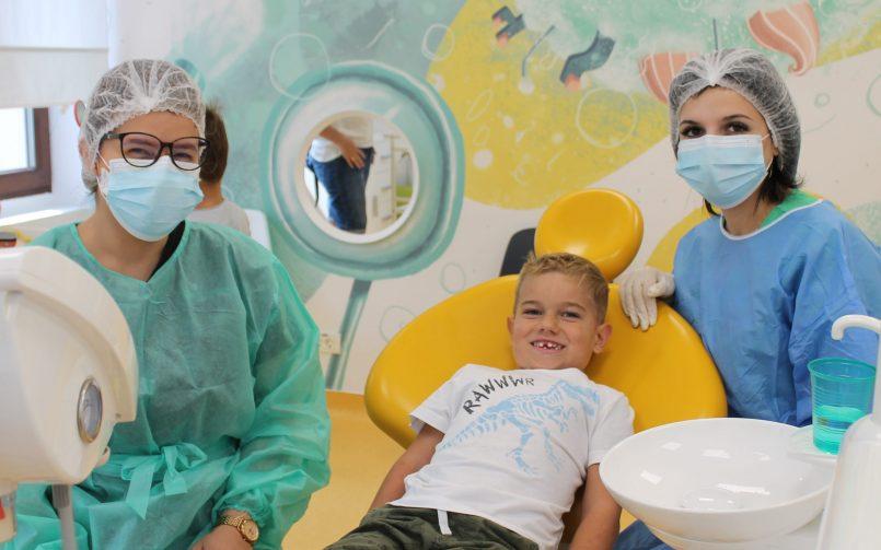 Medic pedodont in stanga, pacient pe scaun si asistenta in dreapta dupa explicarea importantei alimentelor pentru dinti sanatosi