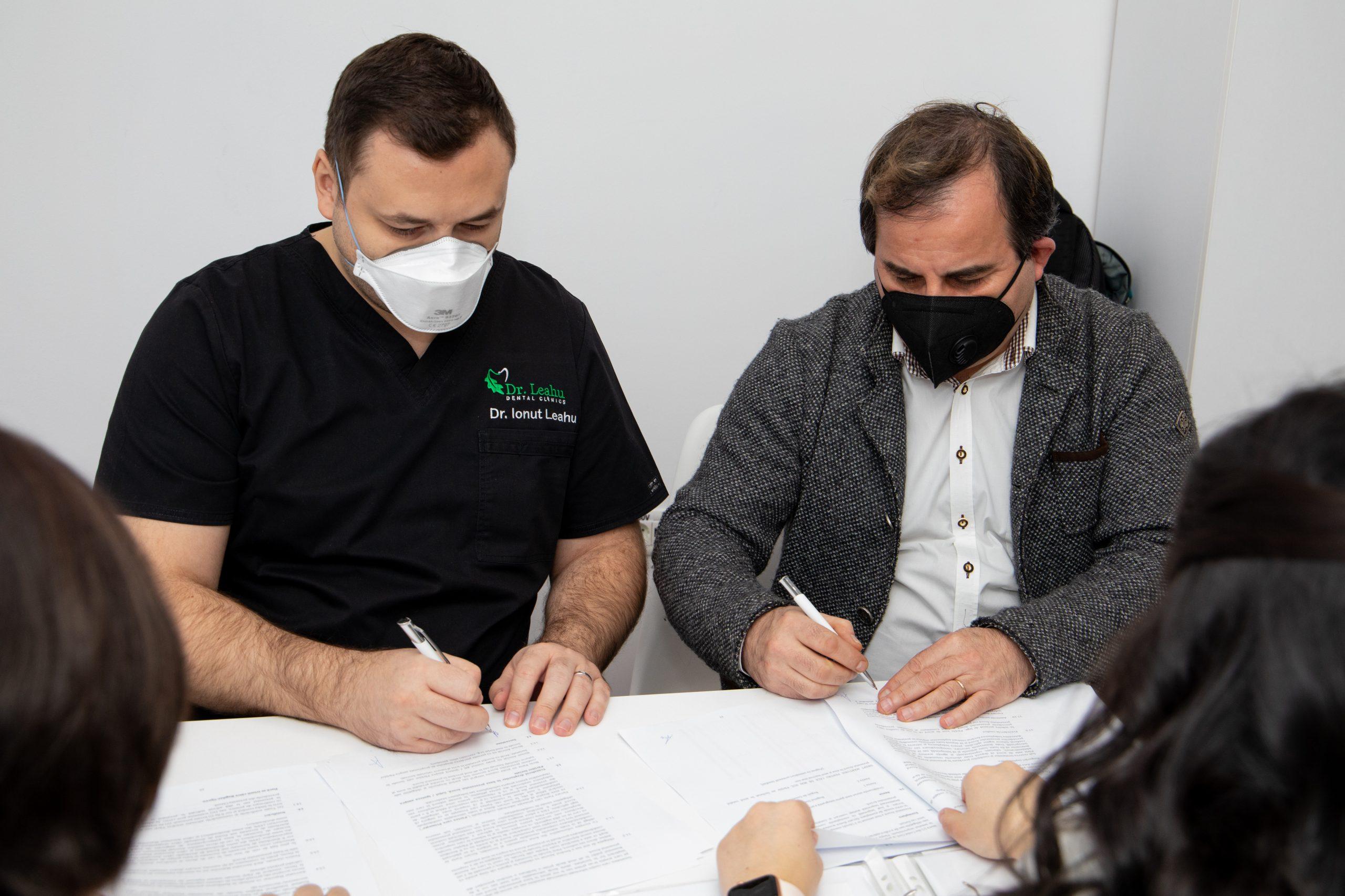 Dr. Ionut Leahu și Dr. Bogdan Oprea semnând parteneriatul