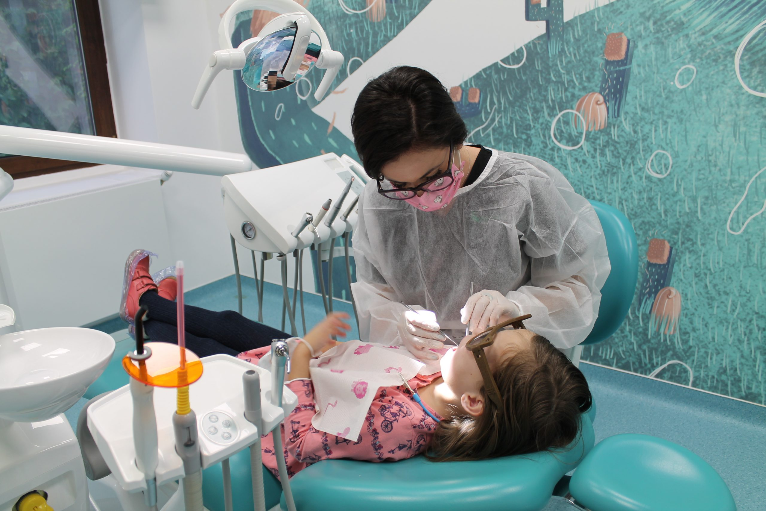 Dr. Iulia Burca in dreapta si pacienta pe scaunul stomatologic in timpul tratamentului