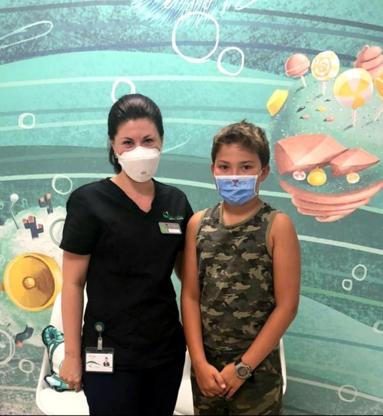 Dr. Elena Boaghe in stanga si pacient copil in dreapta langa un perete colorat