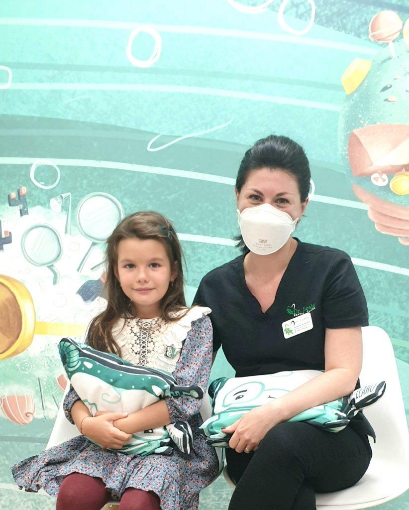 Dr. Elena Boaghe in dreapta pe scaun si pacient copil pe scaun in stanga