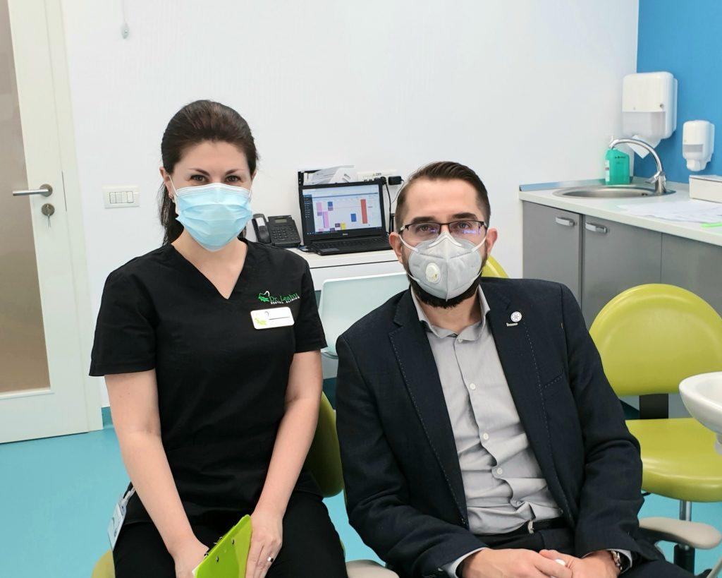 Dr. Elena Boaghe in stanga pe scaun si pacient in dreapta pe scaun stomatologic