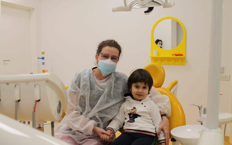 medic pedodont in stanga pe scaun si pacient copil in dreapta pe scaun la control dentitie copii