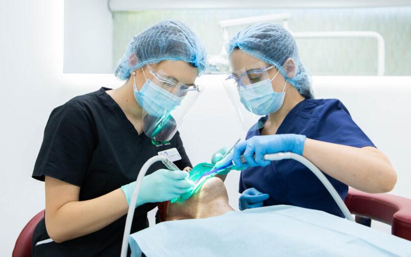 medic stomatolog in stanga, pacient pe scaun, asistent medical in dreapta